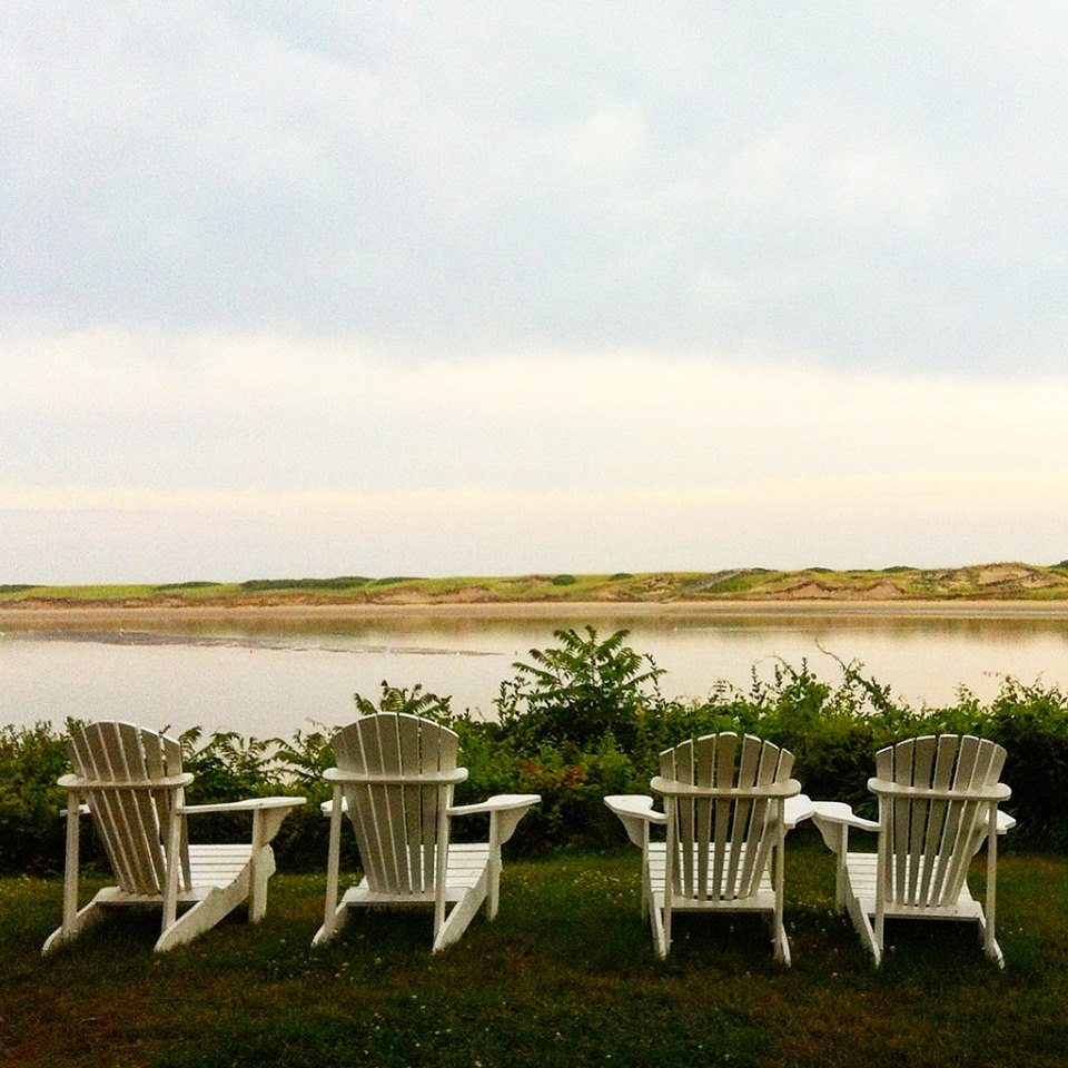 row of four adirondack chairs by the water
