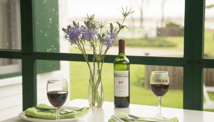 close up of wine glasses and vase of flowers