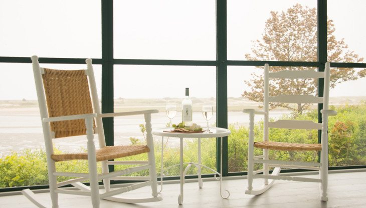 two chairs with a bottle of wine on a screened in porch
